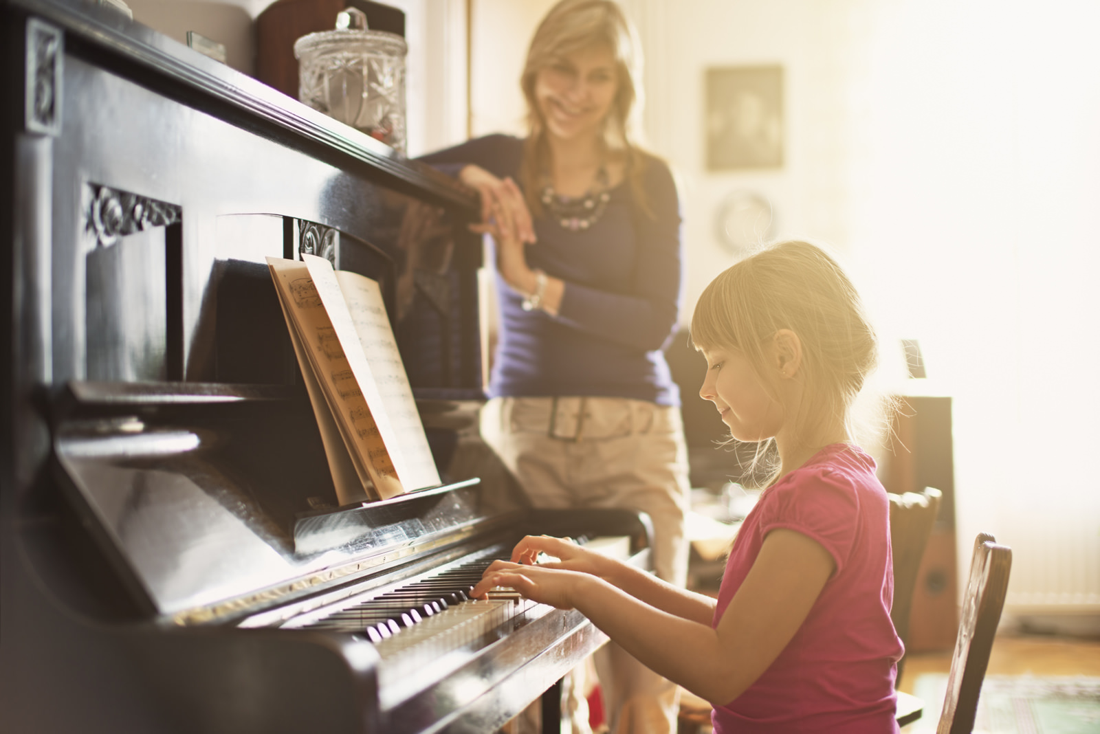 Background image of a young girl playing the piano
