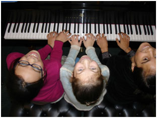 three kids at digital piano